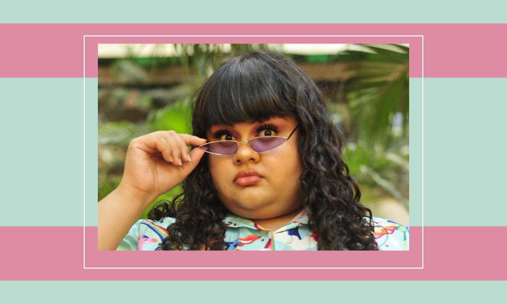 Image of comedian Supriya Joshi holding her glasses on her nose.